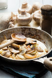 Sliced mushrooms with onion on a pan Royalty Free Stock Photos