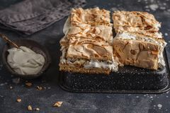 Sliced Norwegian cake with meringue and whipped cream, dark back. Cake with meringue and whipped cream, dark background Royalty Free Stock Photography