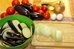 Sliced onion on a cutting board and eggplant soaked in salted wa. Ter in a bowl. Fresh vegetables for cooking light dinner, Moussaka - a traditional Greek dish Royalty Free Stock Photography
