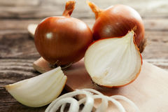 A sliced onion and fresh onions on cutting board Royalty Free Stock Photos