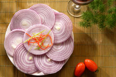 Sliced onion platter. A platter of sliced onions on a bamboo place mat with a glass of wine Royalty Free Stock Photo