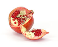 Sliced open pomegranate showing seeds. A fresh pomegranate that has been cut open to show the seeds and pulp on a white background royalty free stock photography