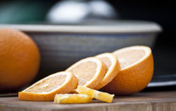 Sliced Orange. Slices of an orange laying on table with blue bowl in background Royalty Free Stock Photos