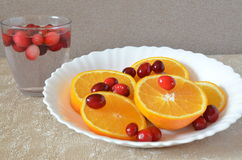 Sliced orange and cranberries on a white plate Royalty Free Stock Photography