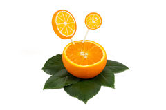 Sliced orange fruit with orange lollipops on green leaves isolated on white Stock Photography