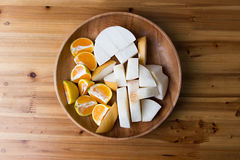 Sliced orange and pear on wooden plate and table royalty free stock photography