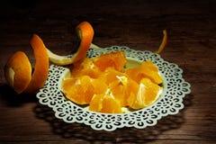 Sliced orange and a peel strip on dark wood Stock Photos