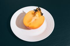 Sliced orange persimmon on a white plate. On a black table Royalty Free Stock Photo