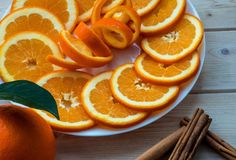 Sliced orange with spiral zest on the plate and cinnamon sticks on the wooden table stock photography