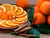 Sliced orange with spiral zest on the plate and groupe of oranges on the wooden table royalty free stock image