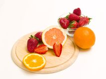 Sliced orange and strawberry. Cut oranges and strawberries on wood plate Royalty Free Stock Photography