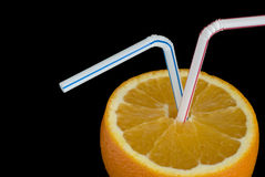 Sliced orange with straws. Inserted against a black background Royalty Free Stock Image