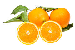 Sliced orange and two oranges Stock Image