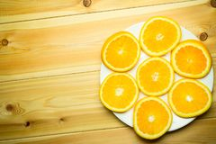 Sliced orange on a white plate. On a wooden background Stock Image