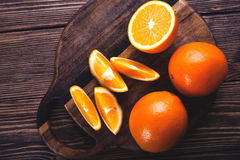 Sliced orange on a wooden table. Top view. Toned. Slices of orange wooden brown bowl on wooden table Stock Image
