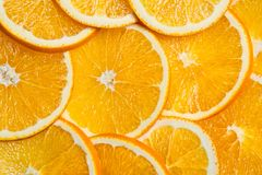 Sliced oranges background, bright fresh fruit cut into even slices Royalty Free Stock Photo