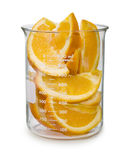 Sliced Oranges In A Beaker. Isolated on white royalty free stock photography