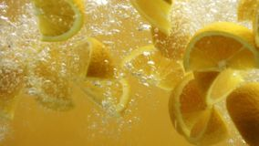 Sliced oranges falling into water close up stock video