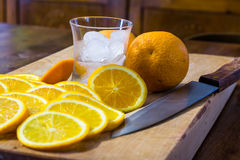 Sliced oranges, a glass full of ice and a knife on a wooden surface Stock Photo