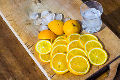 Sliced oranges and a glass full of ice on a wooden surface Stock Photo