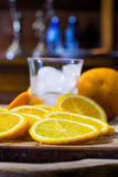Sliced oranges and a glass full of ice on a wooden surface Royalty Free Stock Photography