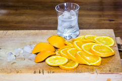 Sliced oranges and a glass full of ice on a wooden surface Royalty Free Stock Images