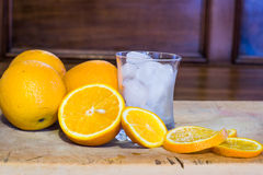 Sliced oranges and a glass full of ice on a wooden surface Royalty Free Stock Image