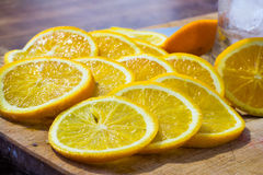 Sliced oranges and a glass full of ice on a wooden surface (close up) Royalty Free Stock Photo