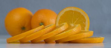 Sliced oranges on a gray-blue background. Close-up Stock Images