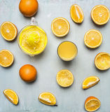 Sliced oranges, a juicer, a glass of juice  wooden rustic background top view close up Royalty Free Stock Images