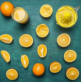 Sliced oranges, a juicer, a glass of juice  wooden rustic background top view close up Stock Image