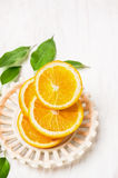 Sliced oranges with leaves in bowl on white wooden Royalty Free Stock Photo