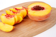 Sliced peaches on wooden board Royalty Free Stock Images