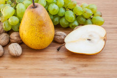 Sliced pear next to green grapes and nuts on wooden background Royalty Free Stock Photos