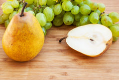 Sliced pear next to green grapes on wooden background Stock Photos