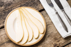 Sliced pear on saucer with silverware on the table Royalty Free Stock Images
