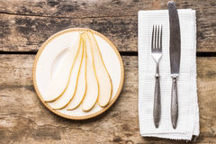 Sliced pear on saucer with silverware on the table Stock Image
