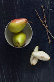 Sliced pears with a bowl on a blue background. With palm branch Stock Images