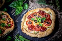 American pizza with mozzarella, tomato, pepperoni on dark wooden table. stock images
