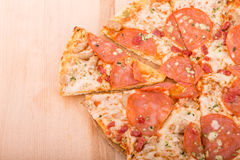 Sliced Pepperoni Pizza on Wood Cutting Board with Copy Space Royalty Free Stock Photo
