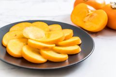 sliced persimmon on plate Stock Images