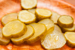 Sliced pickle. Sliced cucumber pickle on a wooden plate Royalty Free Stock Photography