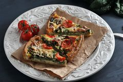 Sliced pie with eggs, fresh spinach, tomatoes, bacon and cheese. Sliced pie  with eggs, fresh spinach, tomatoes, bacon and cheese Stock Photos