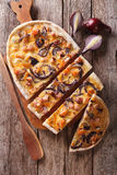 Sliced pie flammkuchen on the table. Vertical top view. Sliced pie flammkuchen with bacon and red onion on the table. Vertical top view royalty free stock photos