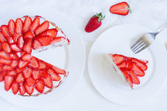 Sliced piece of gourmet homemade celebration. Strawberry cake sweet dessert food with whipped cream and fresh strawberries on white kitchen table background Royalty Free Stock Image
