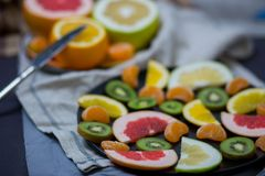 Sliced pieces of citrus fruits are black two big plates of halves, blue gray stock image