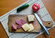Sliced pieces of sausage and cheese. On a wooden cutting board along with a cucumber and a tomato Stock Photos