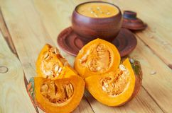 Sliced pieces of yellow pumpkin close up. Homemade pumpkin soup on the blurred background. Traditional autumn food or thanksgiving. Dish. Side view Royalty Free Stock Photo