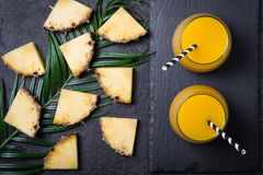 Sliced pineapple and pineapple juice or smoothies on a black background.  royalty free stock photography