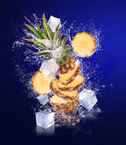 Sliced Pineapple in water splashes with ice cubes Royalty Free Stock Image
